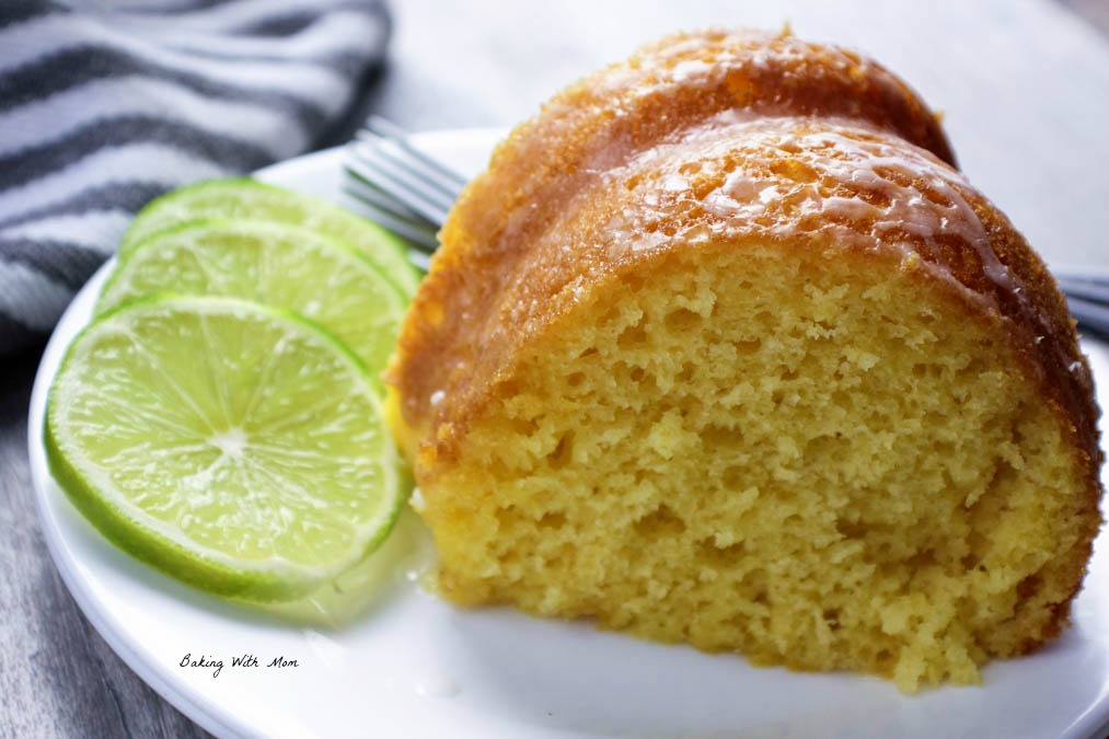 Piece of key lime cake on a white plate with sliced limes