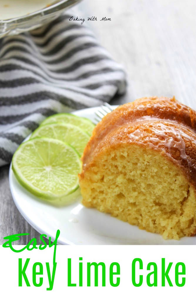 Key lime cake slice on a white plate with a striped towel and lime slices