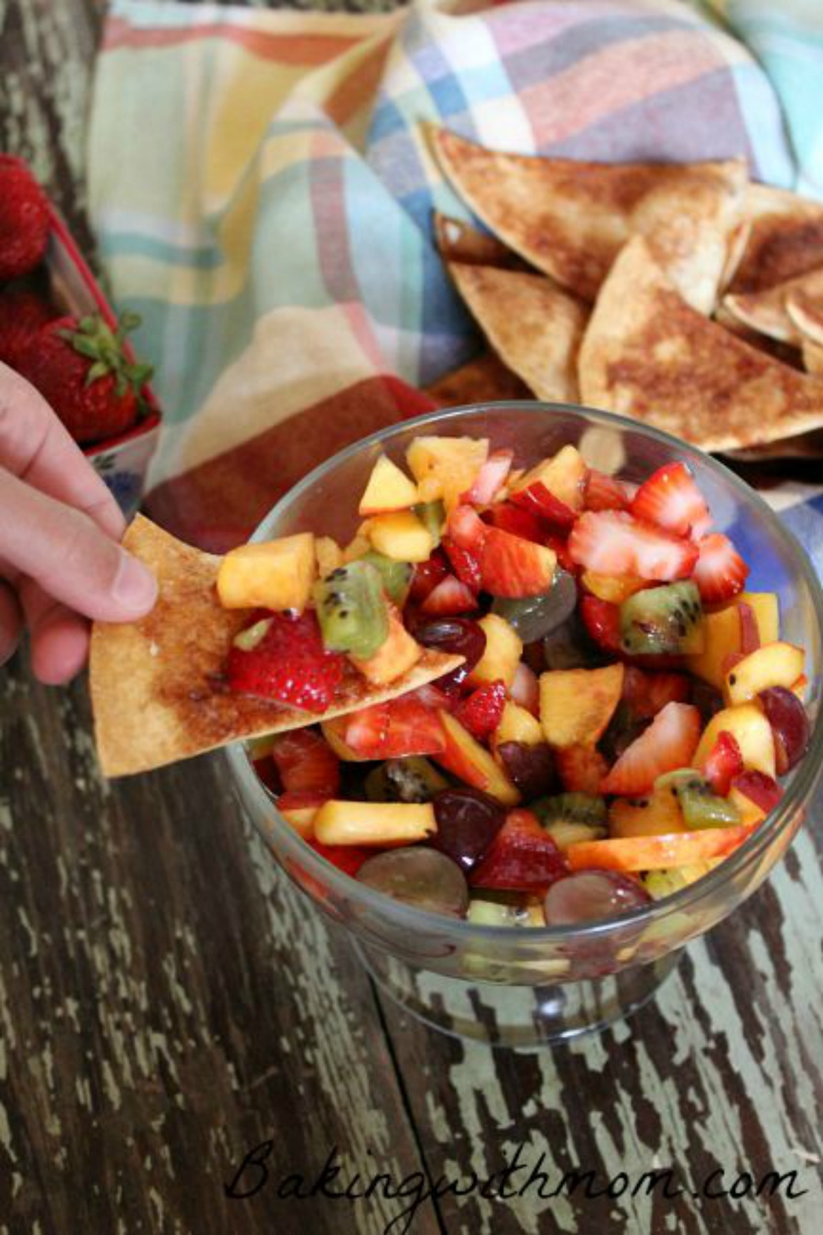 chopped fruit in a clear bowl with cinnamon chips lying in the background