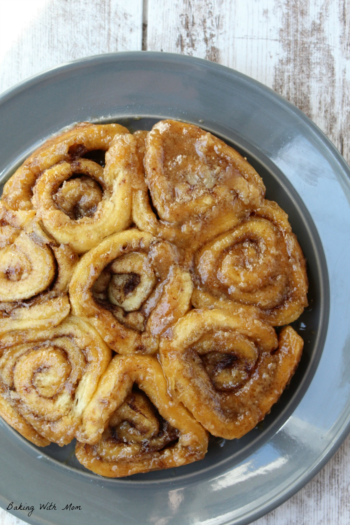 Cinnamon rolls on a gray plate with toppings of brown sugar