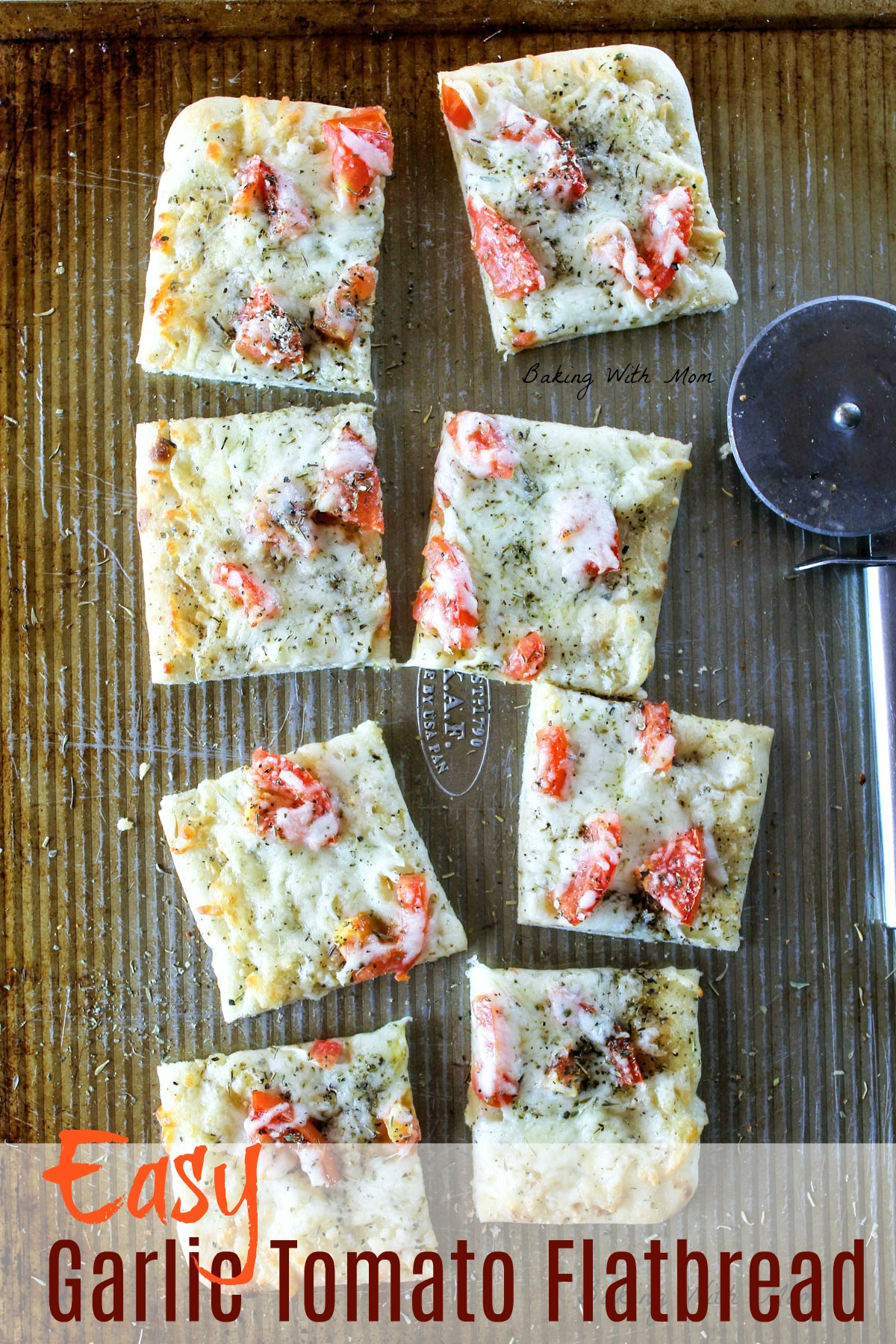 Slices of flatbread on a baking sheet with mozzarella cheese, Italian seasoning and tomatoes