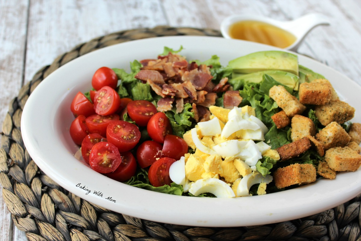 lettuce salad in a white bowl with tomatoes, hard boiled eggs, bacon, slices of avocado and croutons