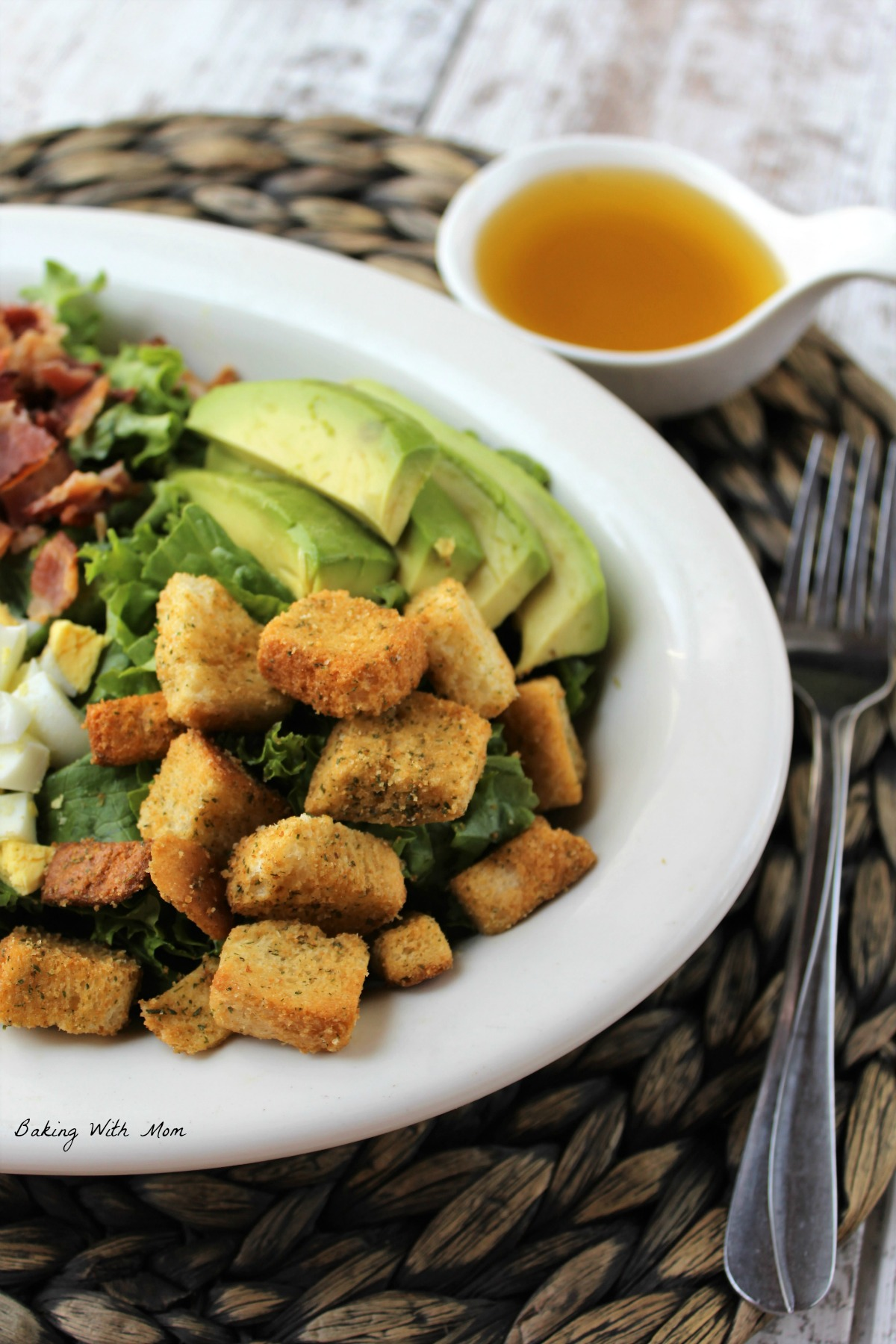 Lettuce salad on a white plate with a fork laying besides. Croutons and avocado on top of salad