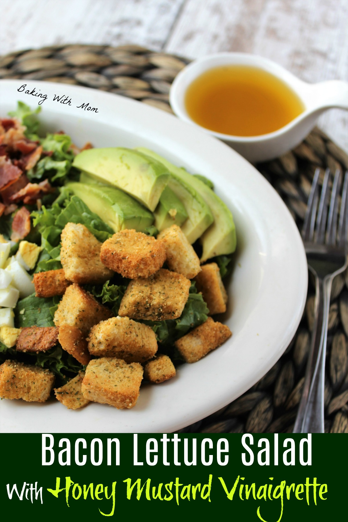 Lettuce salad in a white bowl with Honey Mustard Dressing besides. Lettuce topped with avocado, bacon, croutons, eggs