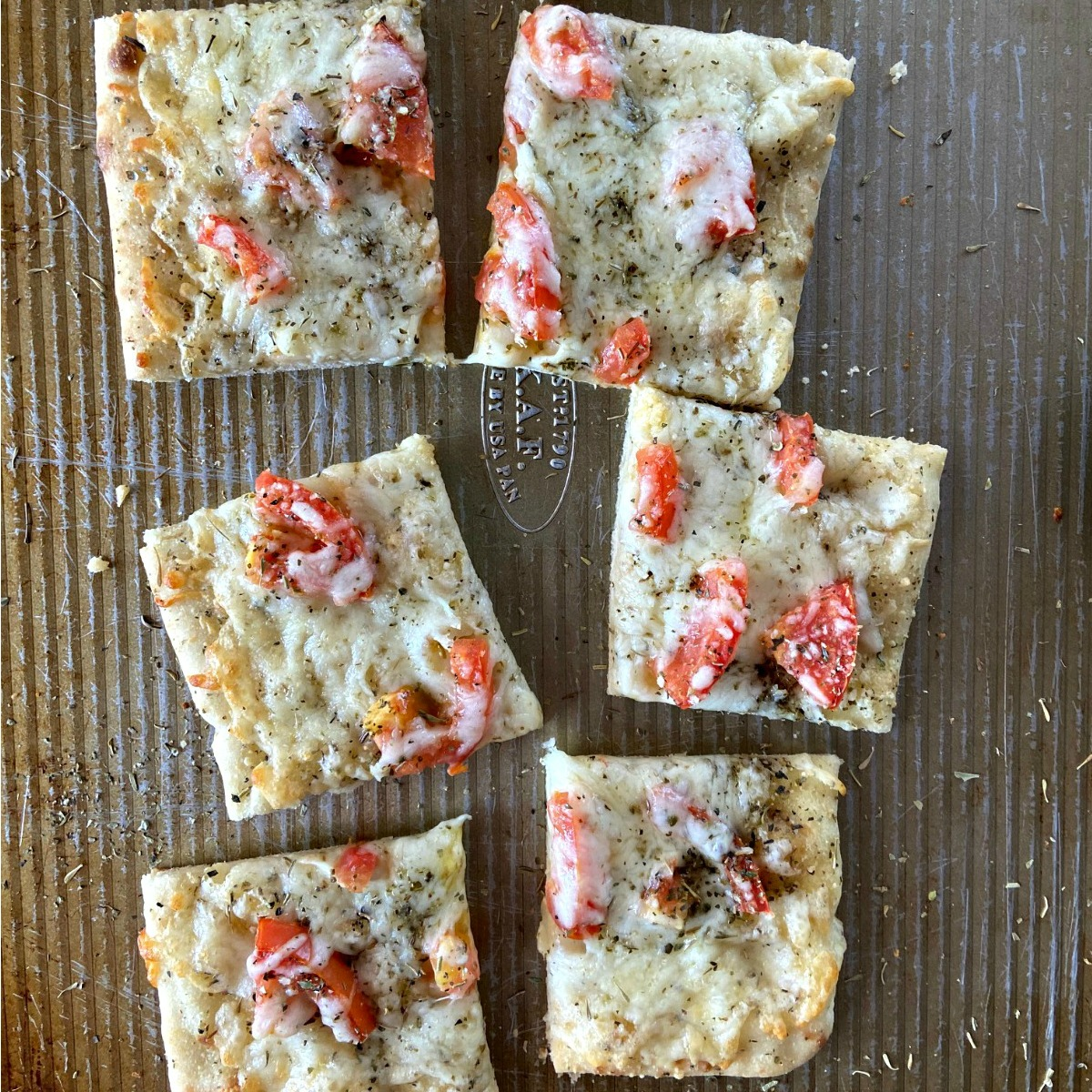 Cut easy garlic tomato flatbread on a cookie sheet