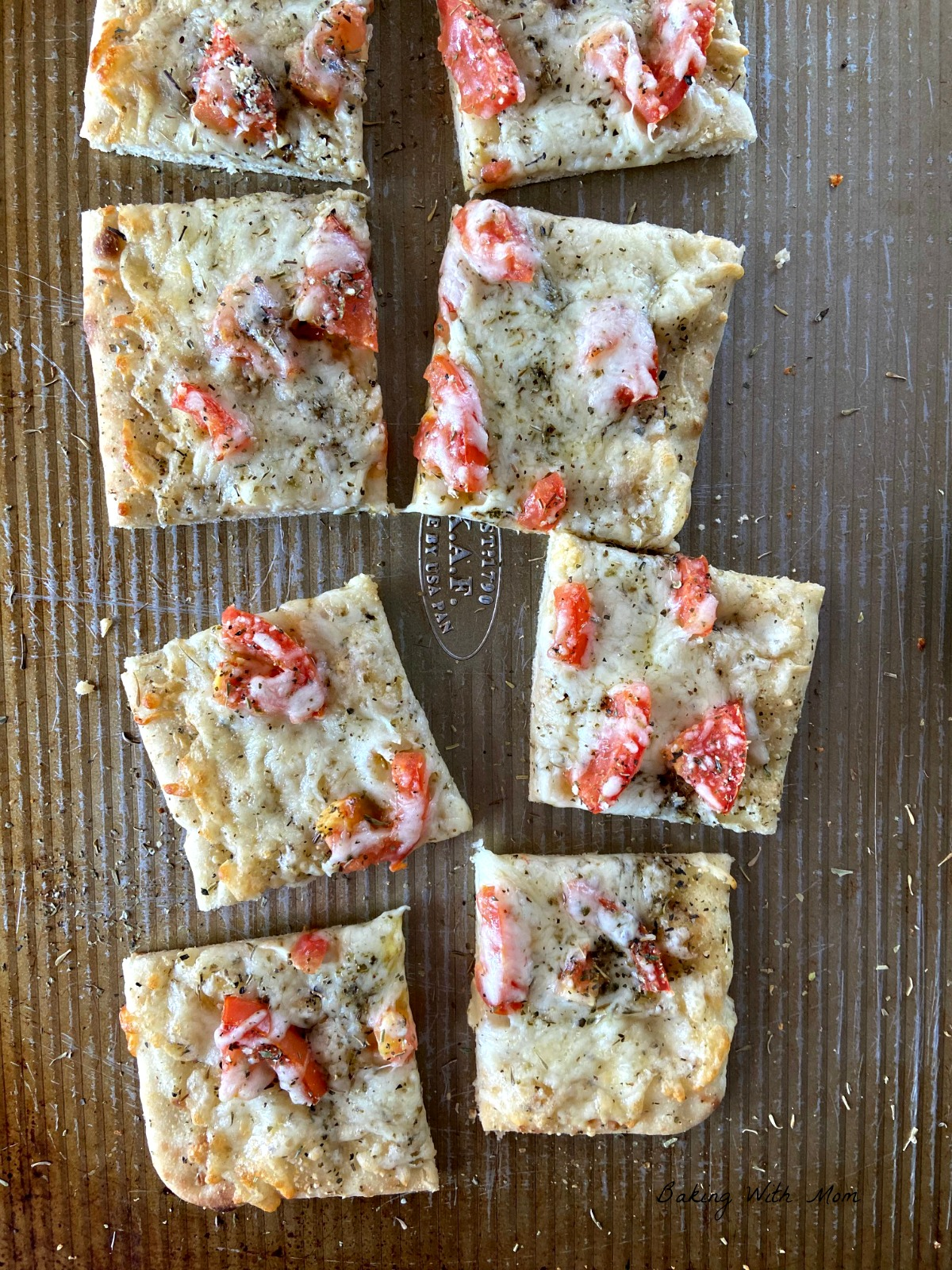 Pieces of flatbread on a baking sheet with tomato, cheese and spices