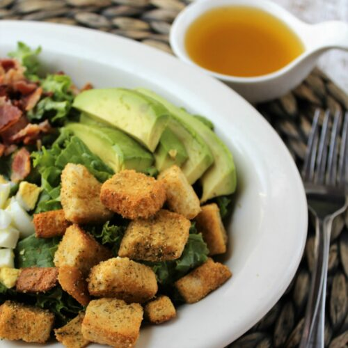 lettuce salad in a white bowl with avocados, croutons, bacon