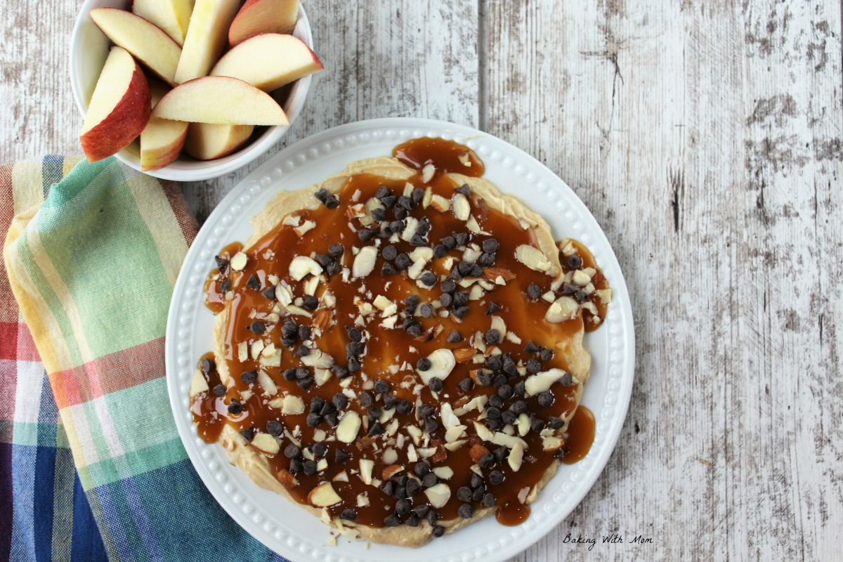 Plate of creamy caramel apple dip topped with chocolate chips, almonds on a white plate