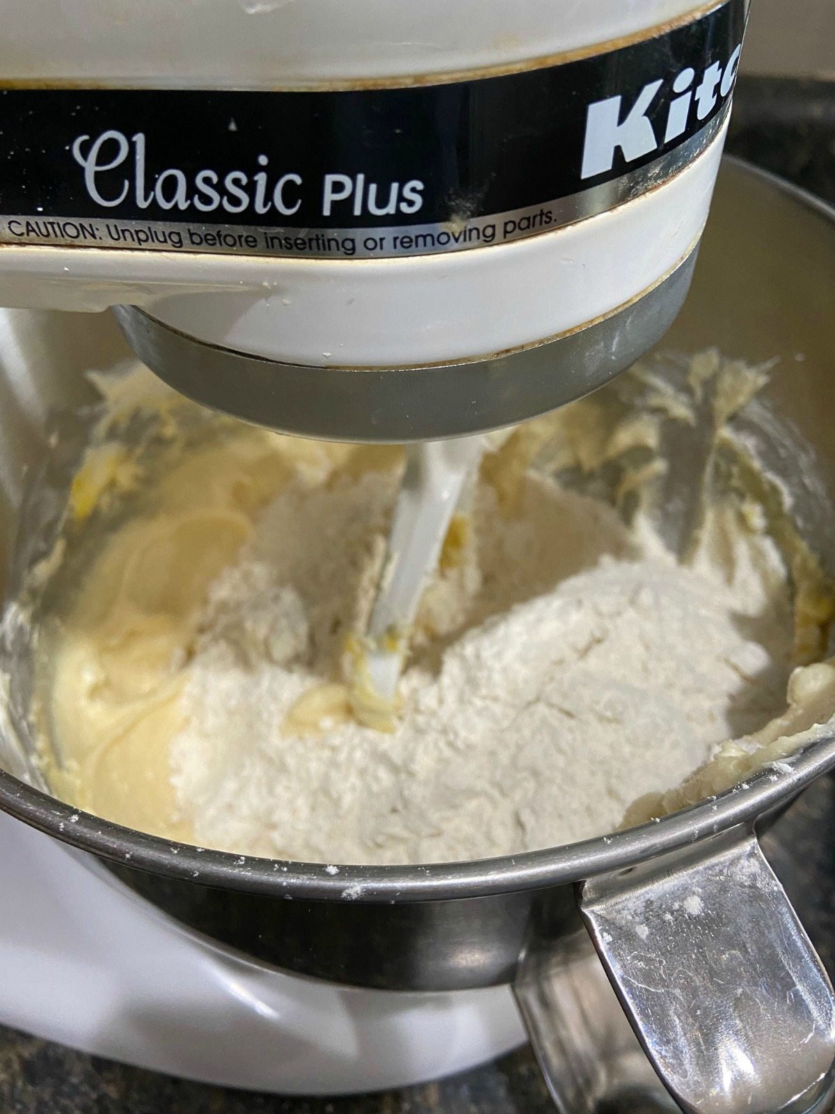 Picture of a stand mixer with cookie dough being mixed.