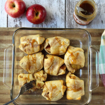 Apples sitting in a square baking dish with caramel drizzled on top covered in dough