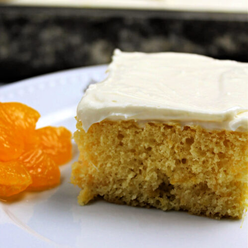 slice of orange cake with cream cheese frosting on a white plate with mandarin oranges