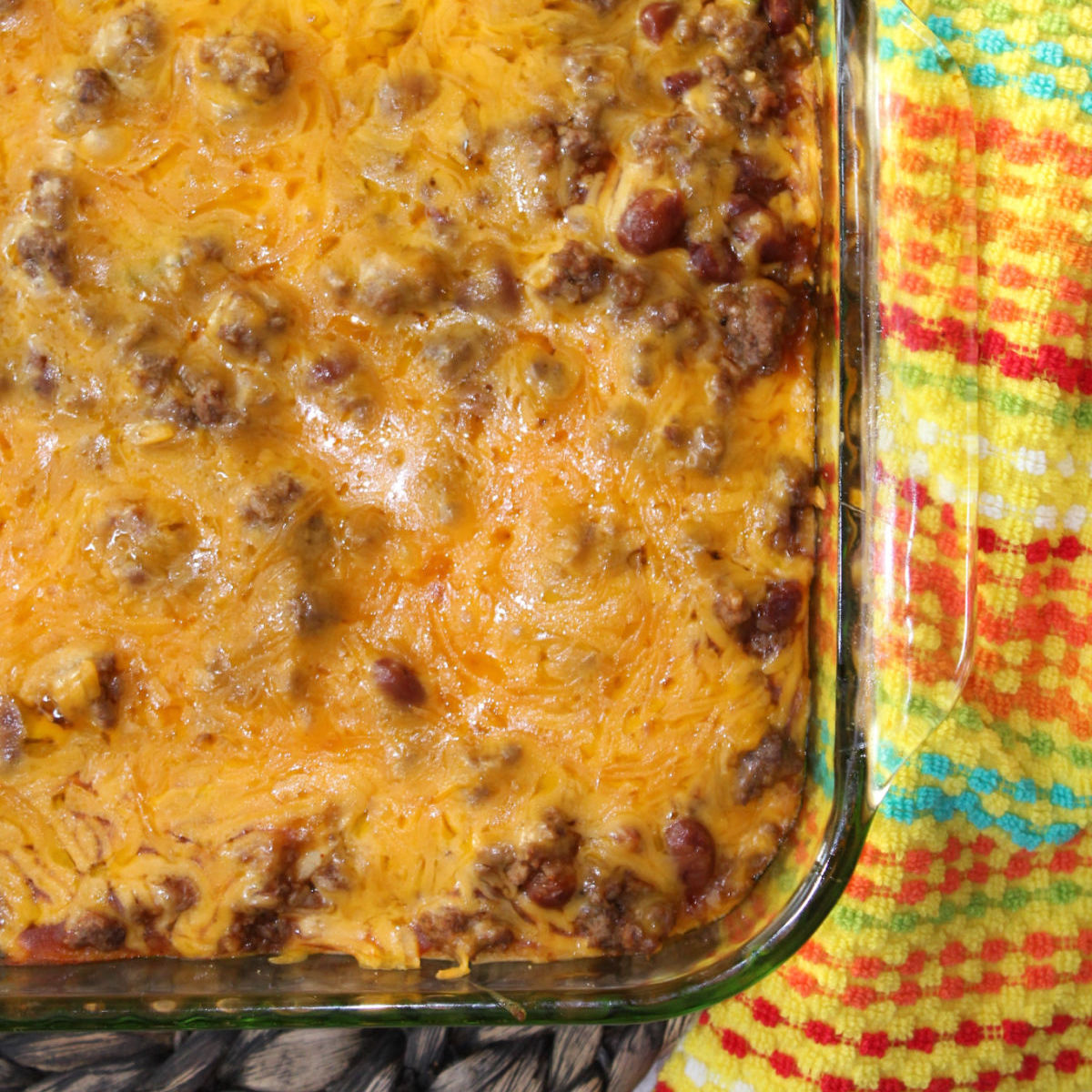 enchilada casserole in a clear casserole dish with beans, hamburger and cheese