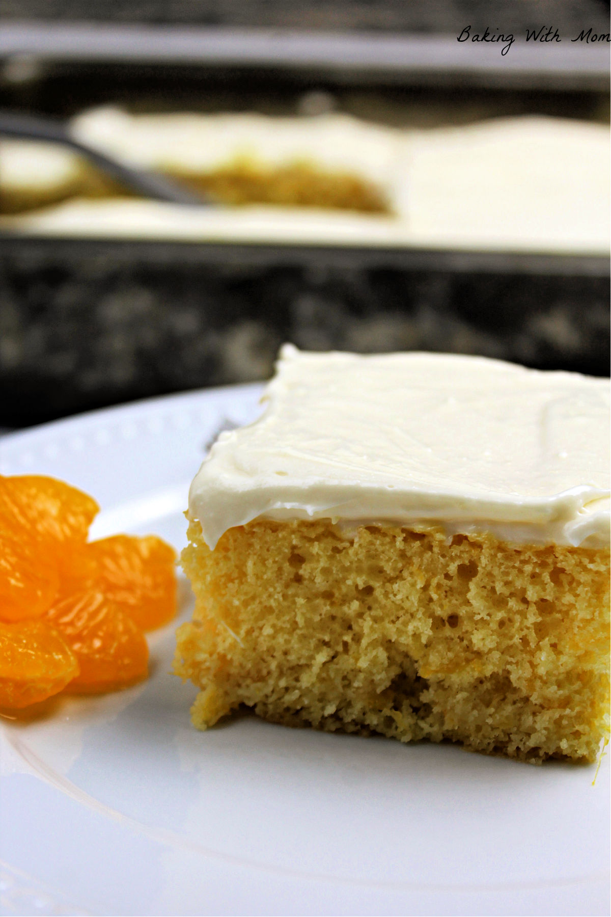 Slice of cake with mandarin oranges besides on a white plate.