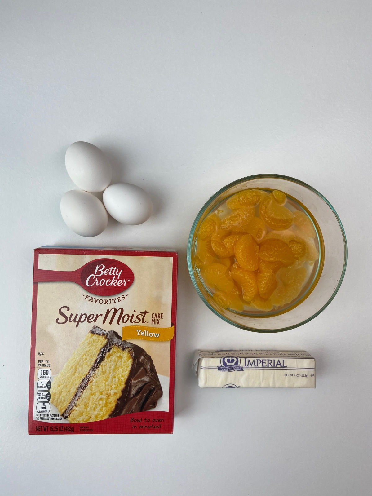 cake mix box, 3 eggs, mandarin oranges in bowl and stick of margarine