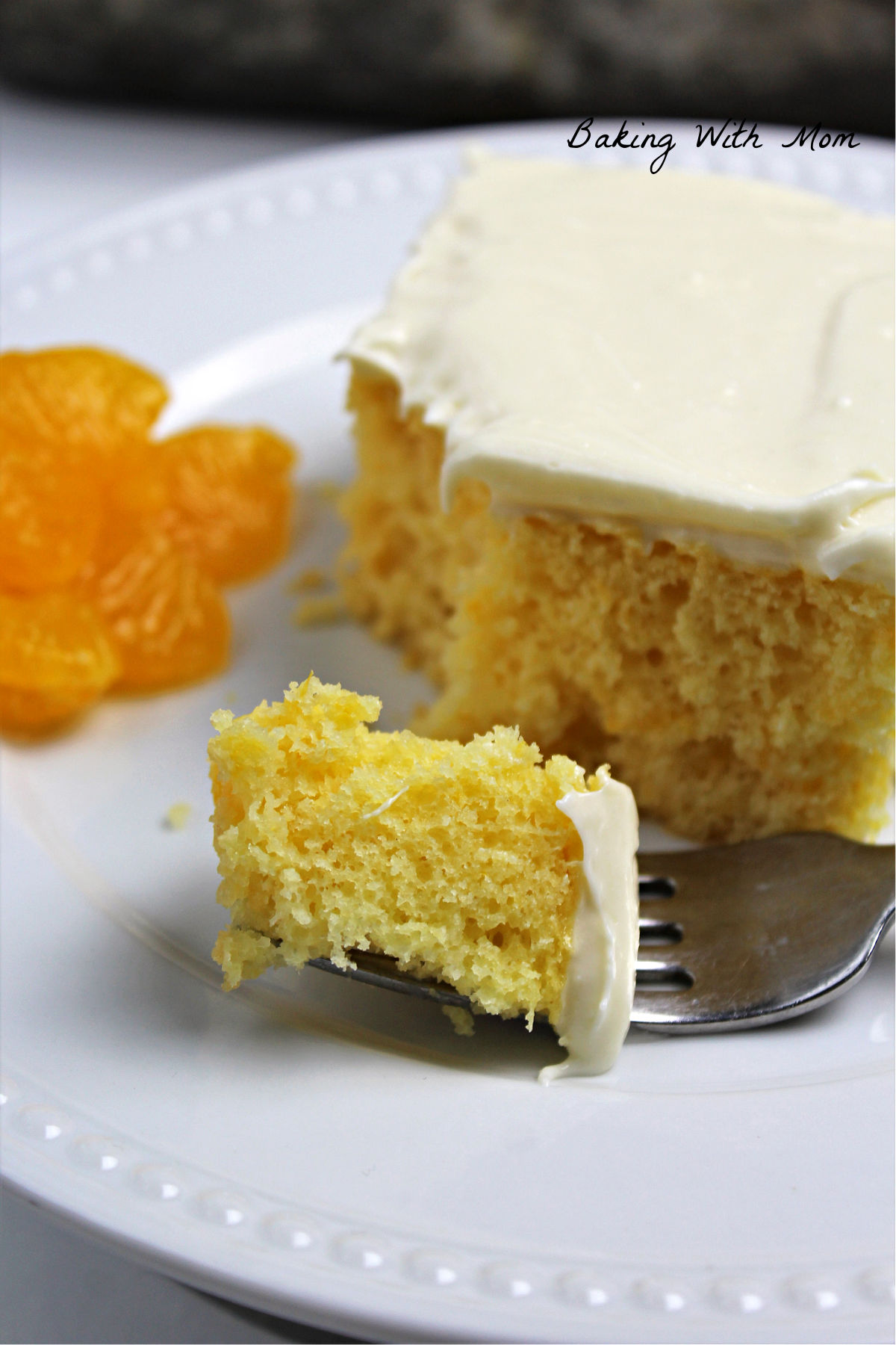 Fork with a piece of mandarin orange cake on it and slice of cake on a white plate.