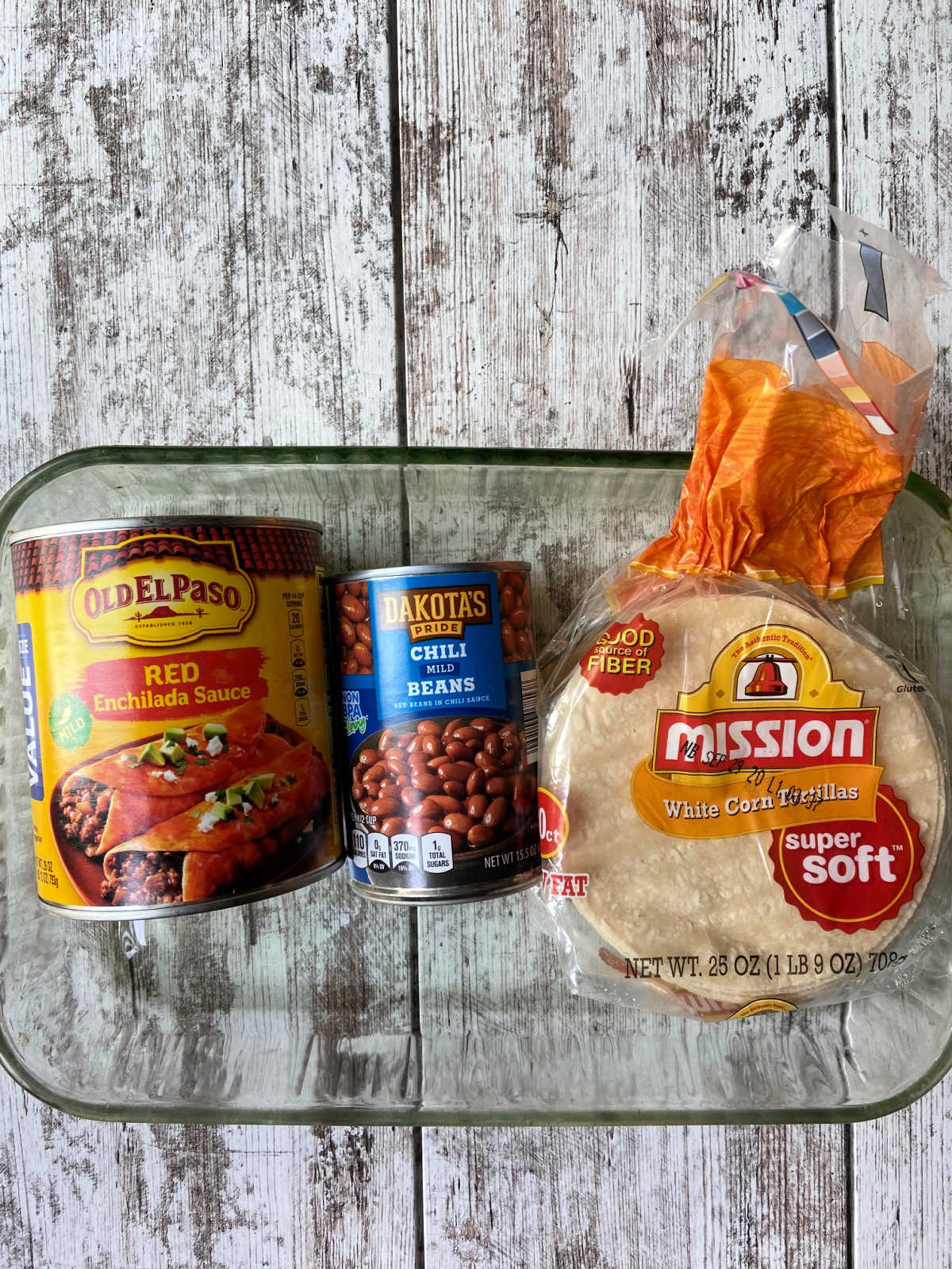 Casserole dish with enchilada sauce, chili beans and corn tortillas in their cans and packages