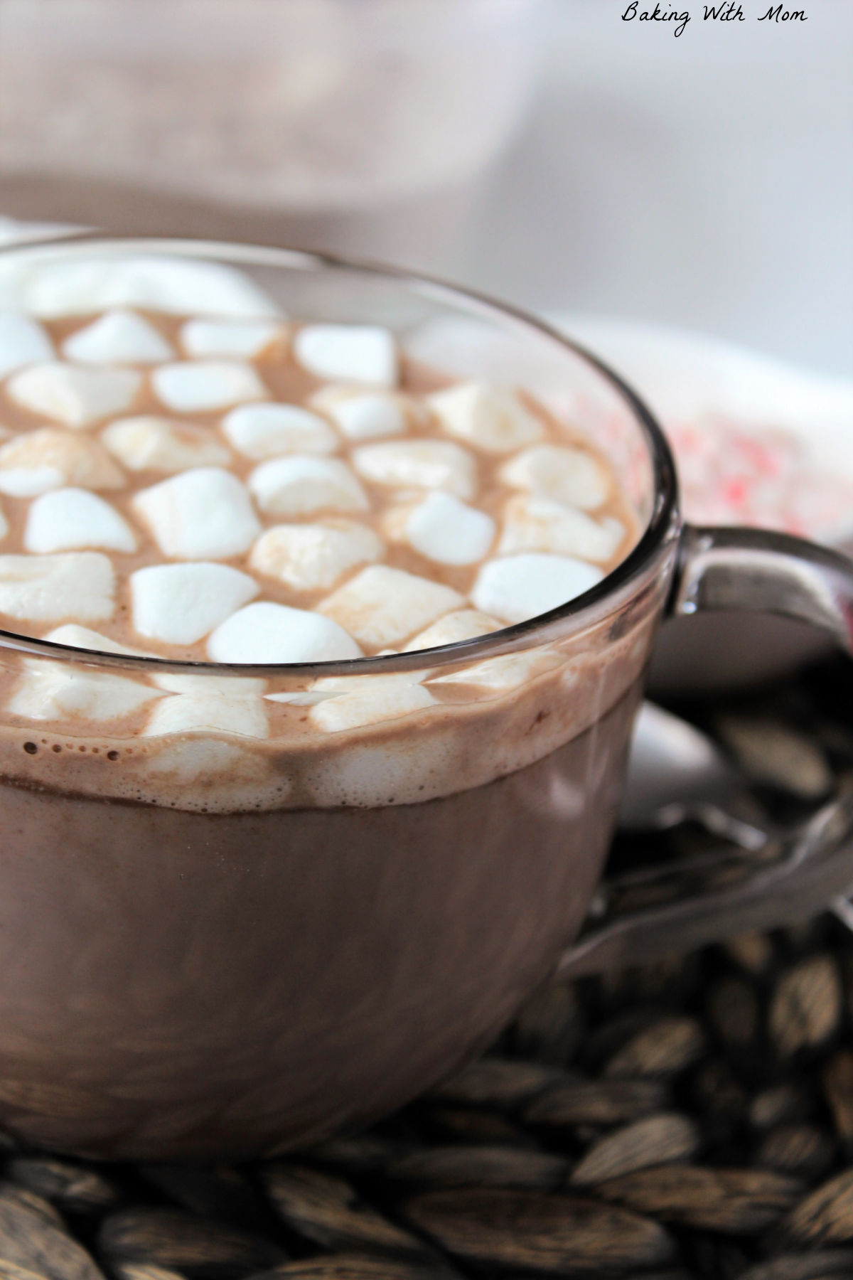 Hot chocolate in a glass cup with marshmallows floating on top