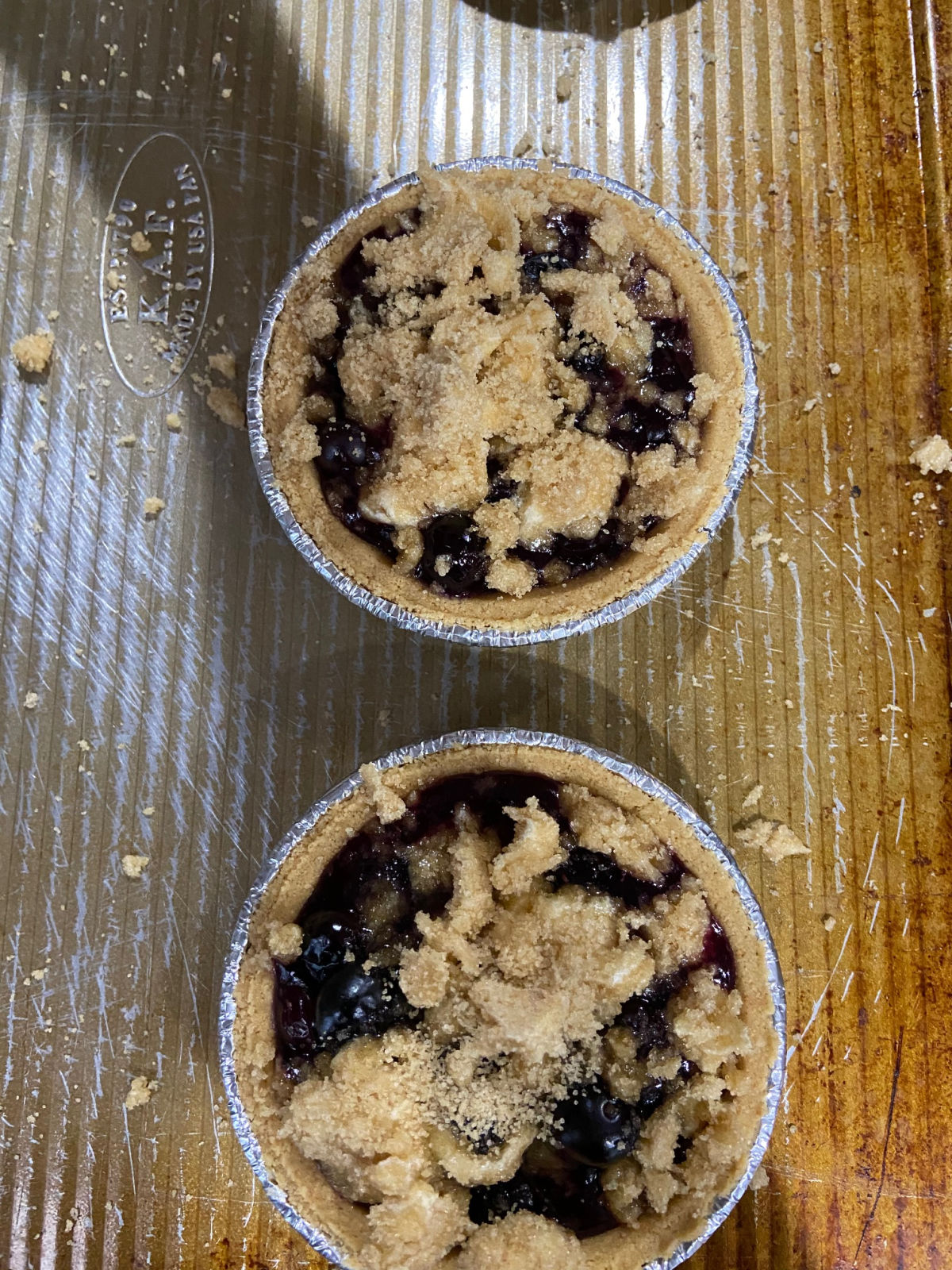 Mini pies on a cooking sheet with uncooked blueberry filling inside.