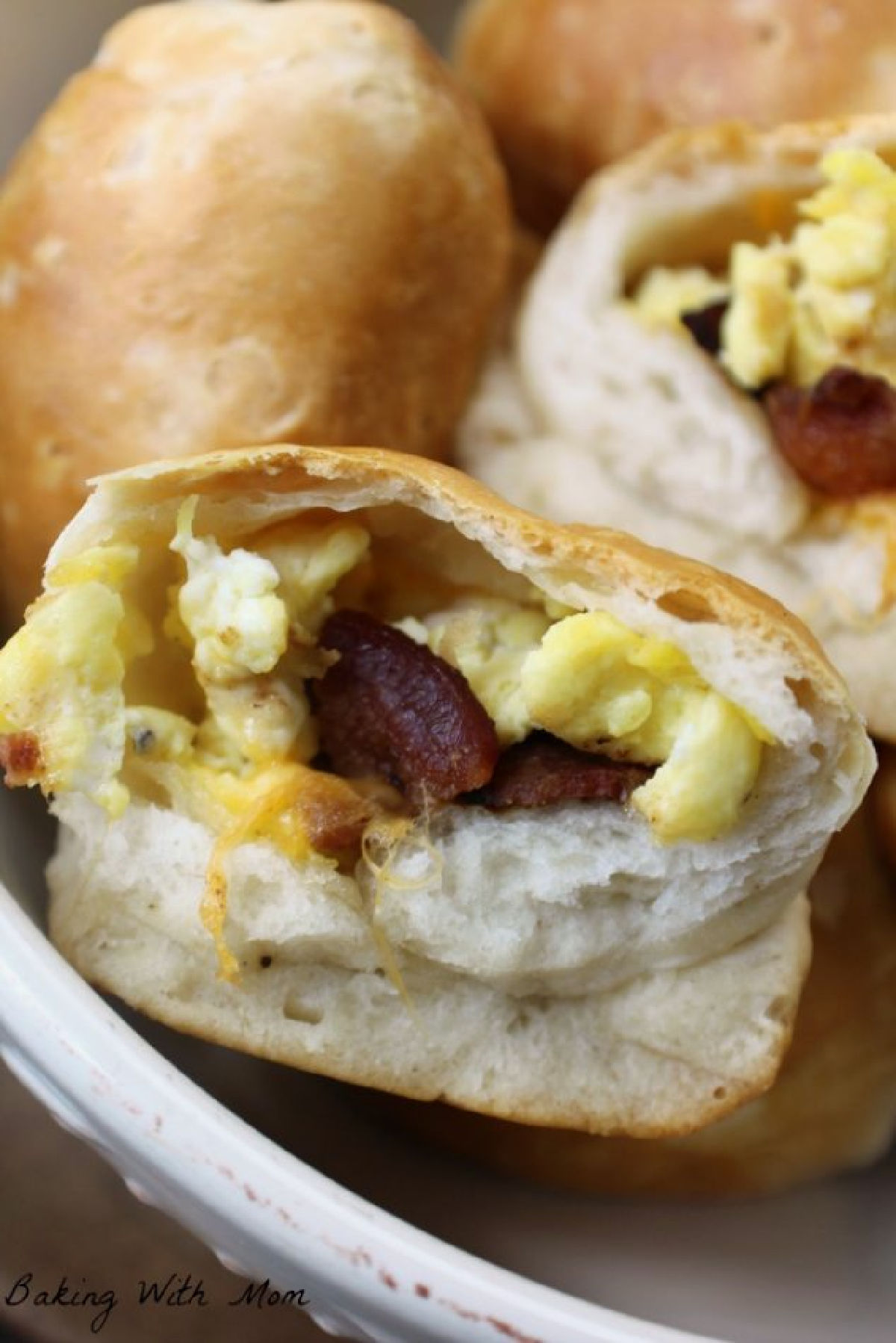 Biscuits stuffed with eggs, bacon, cheese in a cream colored bowl.