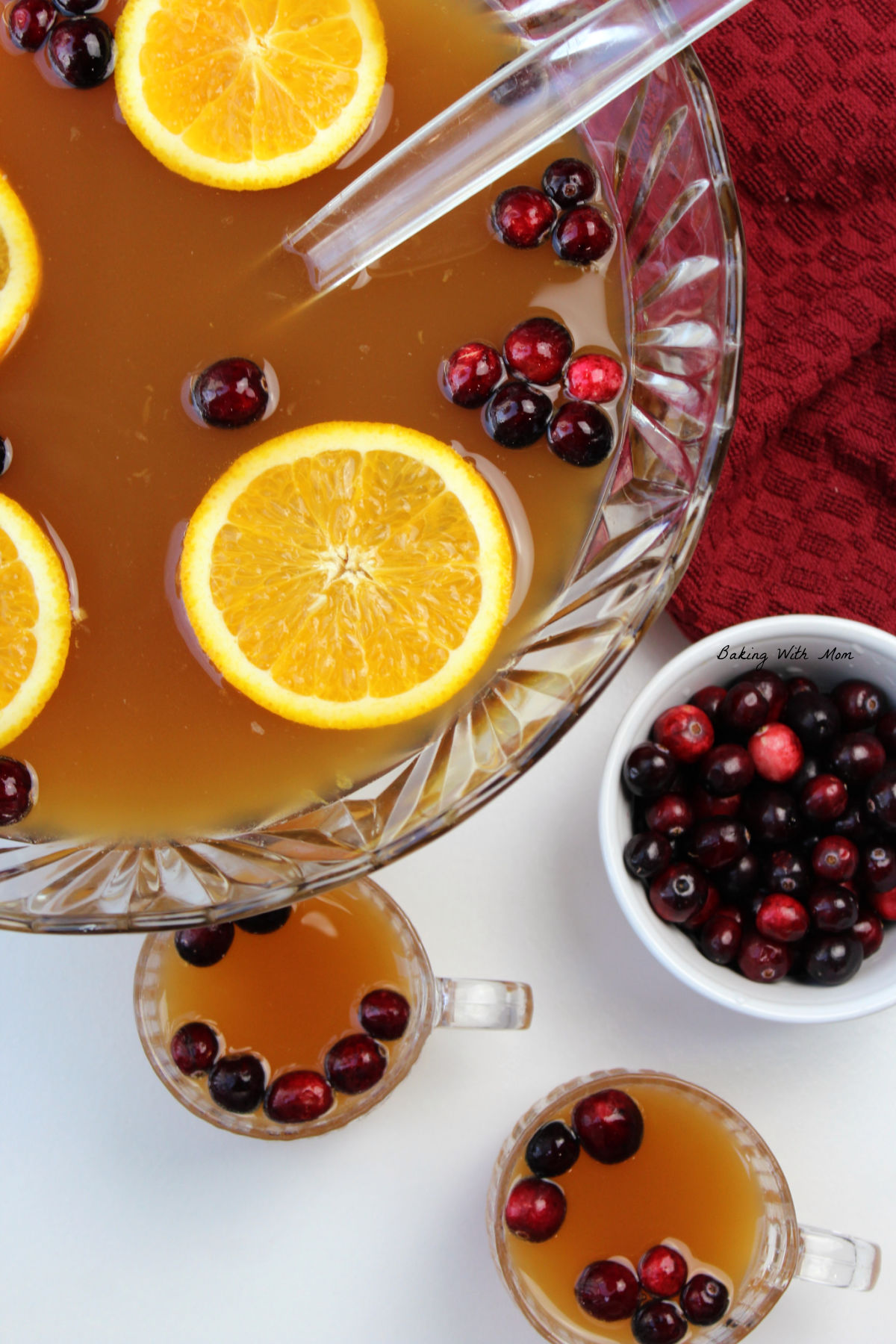 Bowl of punch with cranberries and orange slices floating on top.