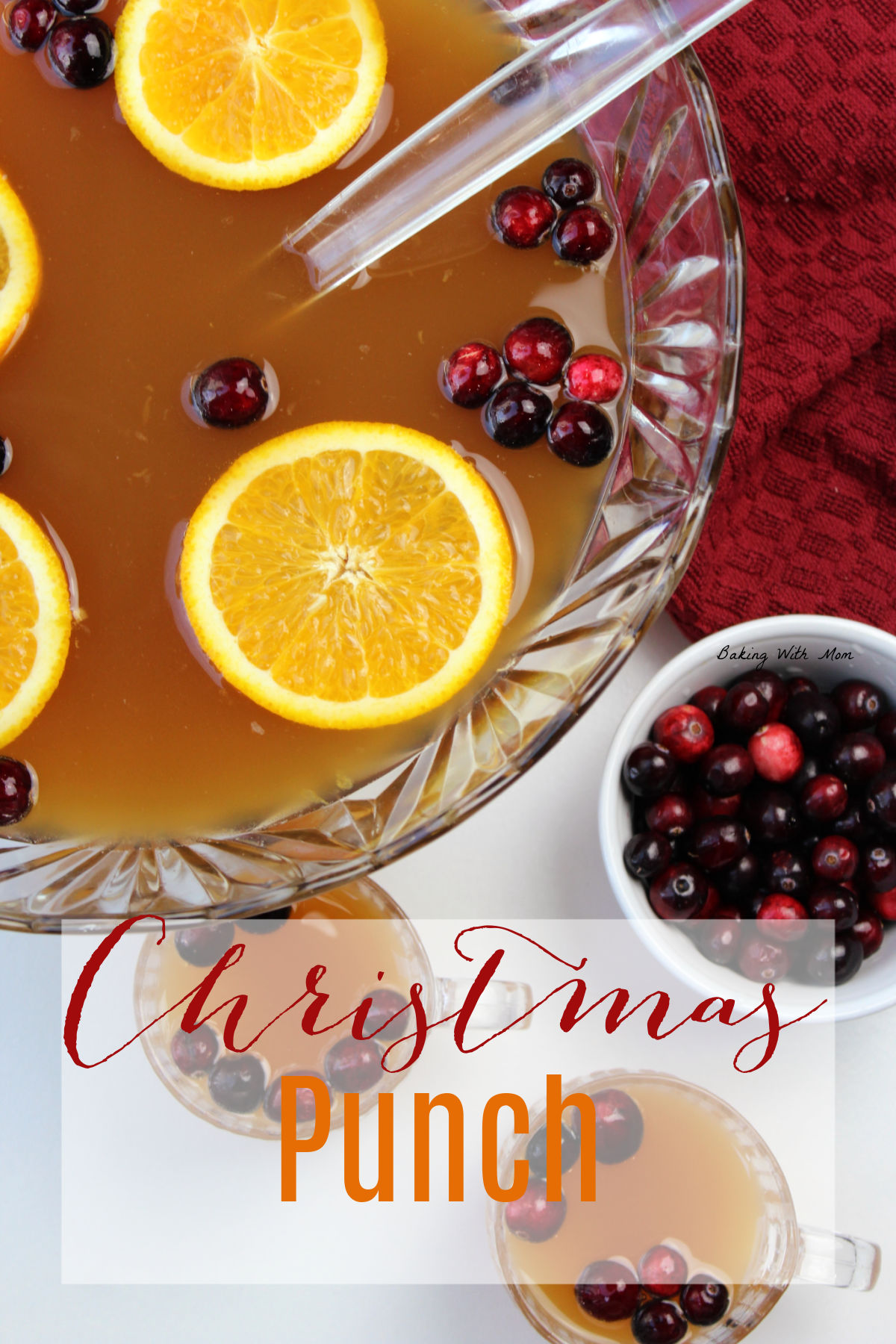 Bowl of punch with oranges and cranberries in a clear bowl with a bowl of cranberries besides.