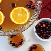 Christmas punch in a clear punch bowl with orange slices and cranberries on top