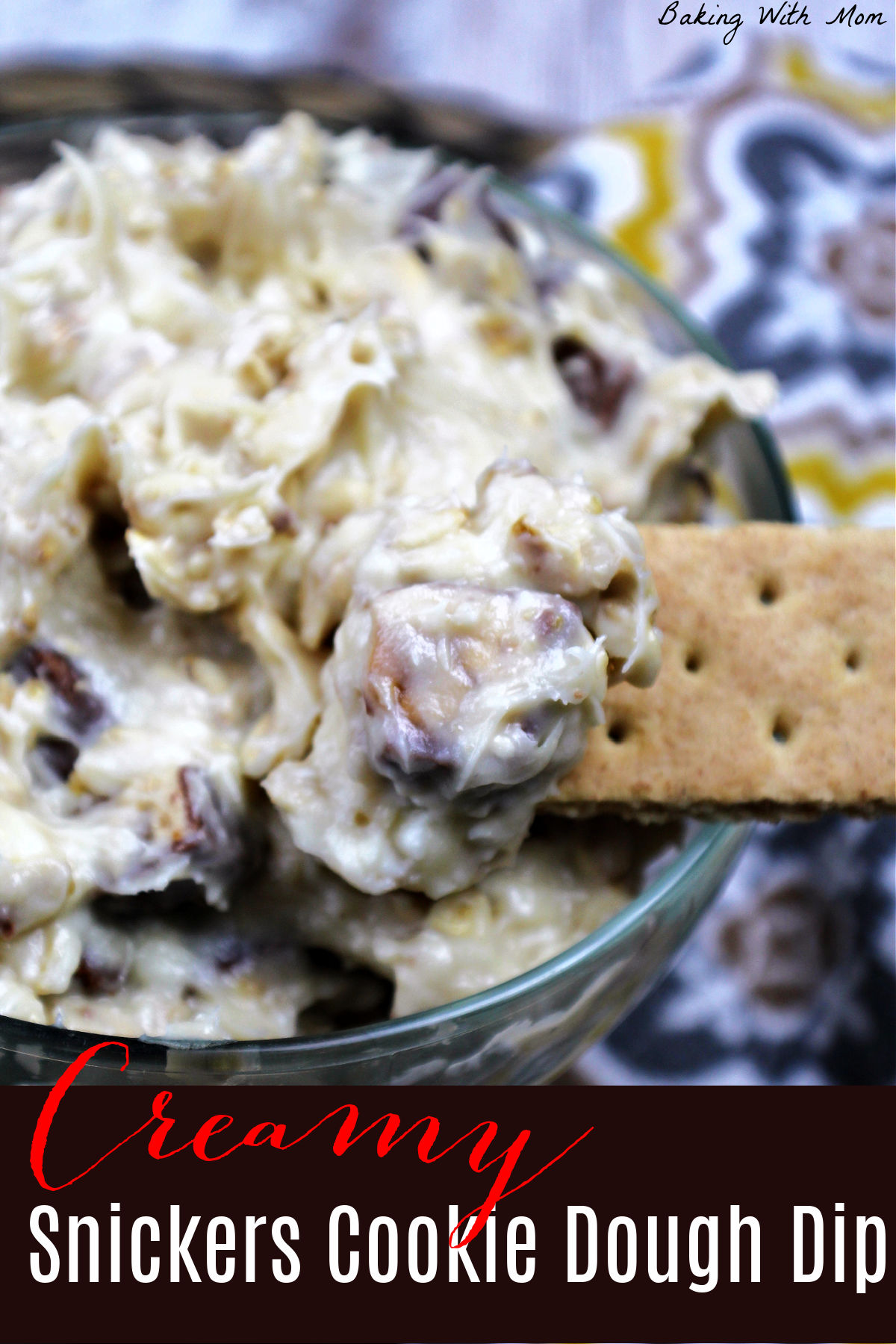 Cookie dough dip with snickers in a clear bowl with a yellow and gray towel laying besides.