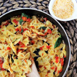 bow tie pasta in a frying pan with spinach and tomatoes