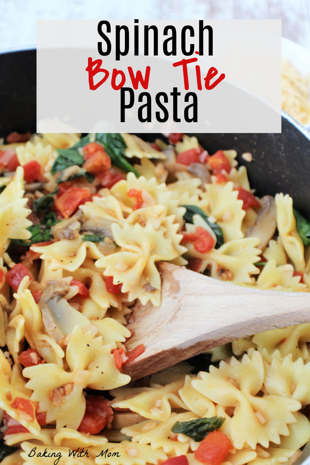 wooden spoon holding pasta and tomatoes with mushrooms and spinach.