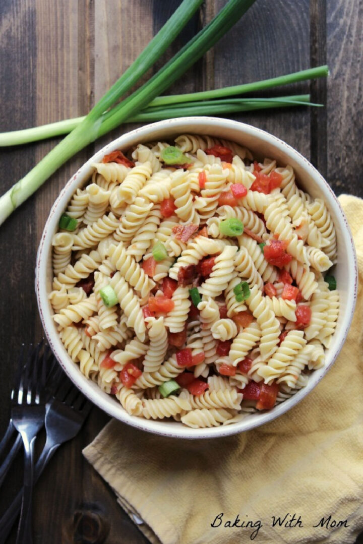 Pasta salad recipe with green onions and tomatoes in a cream colored bowl with green onions laying besides.