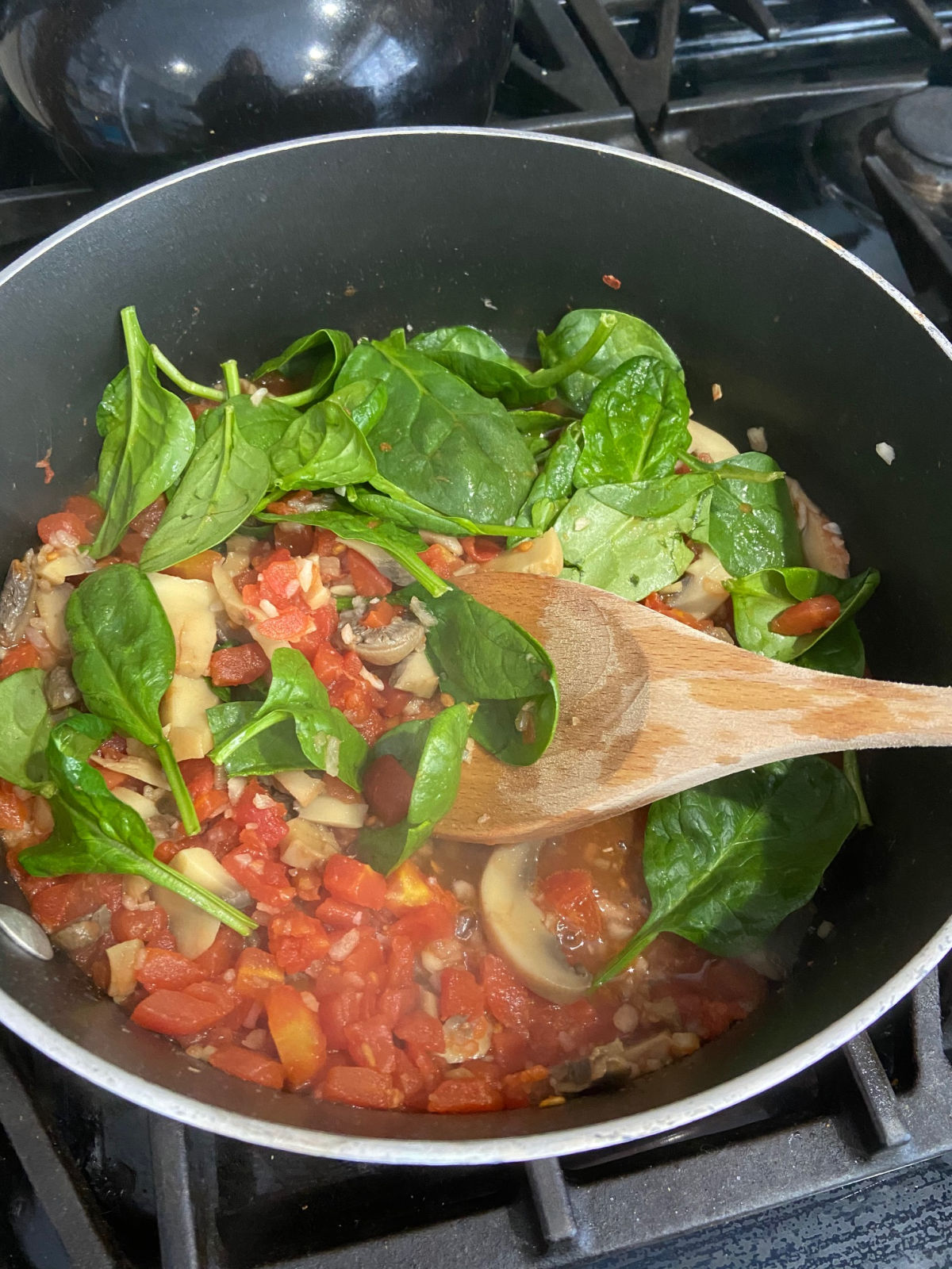 fresh spinach in a frying pan with tomatoes and mushrooms.