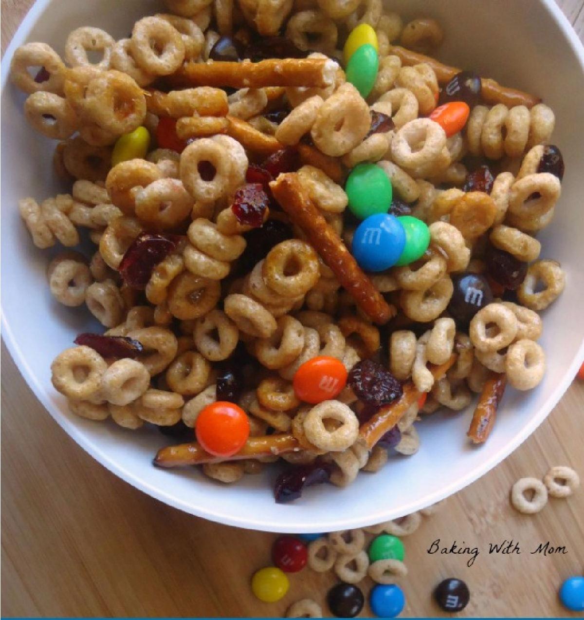 cheerios, m&m's, pretzels in a white bowl