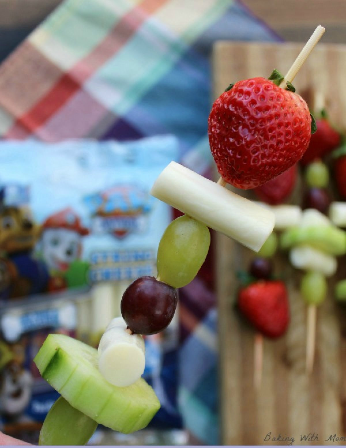 Easy snack kabobs with cucumbers, cheese, grapes and strawberries on a kabob stick.