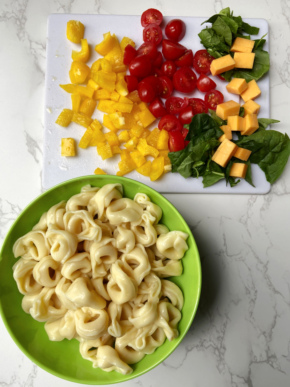 Bowl of cooked tortellini and chopped peppers, spinach, tomatoes and cheese.