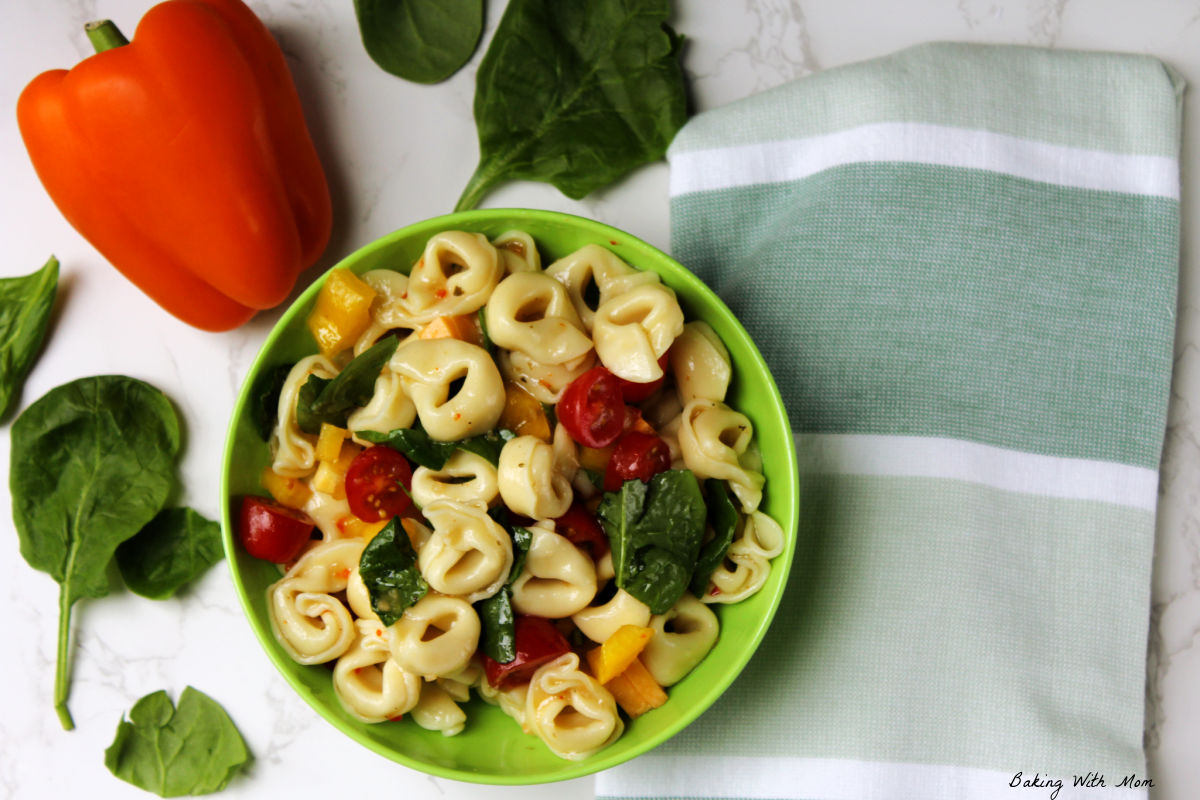 Bowl of tortellini salad with a towel, orange pepper and spinach laying besides.