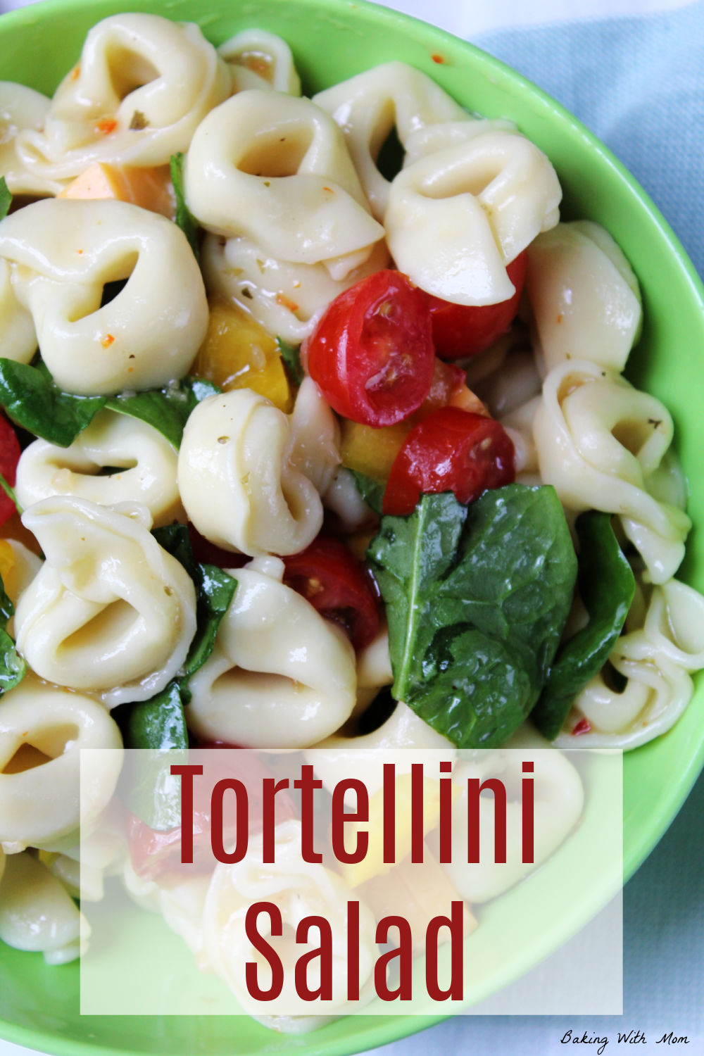 Bowl of tortellini, spinach, tomatoes in a green bowl.