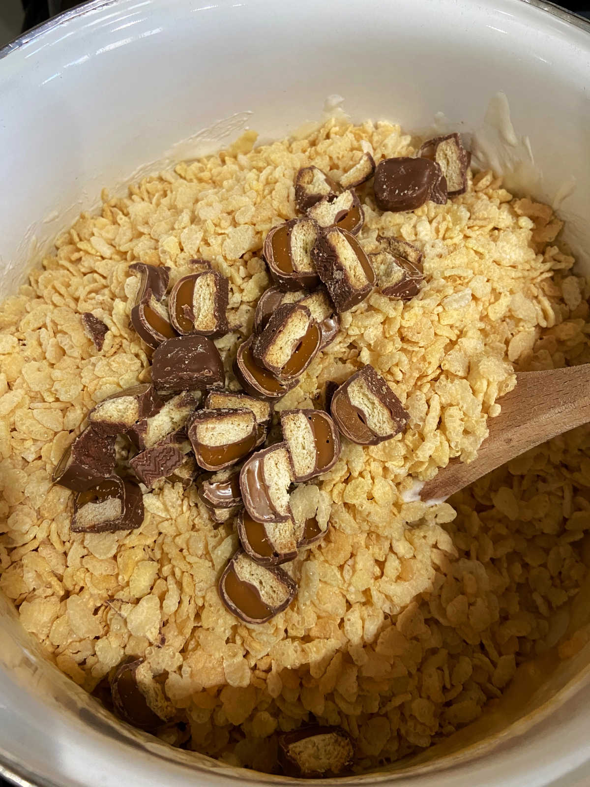 Adding the chopped Twix bars to Rice Krispie cereal.