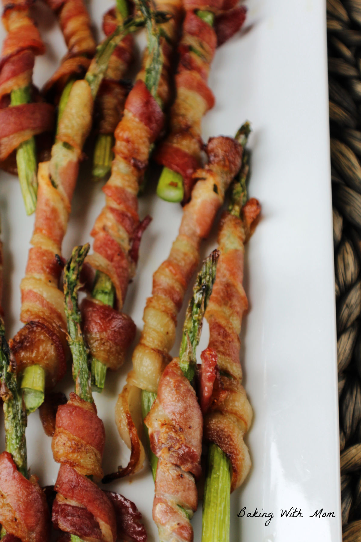 Asparagus wrapped in bacon on a white plate.