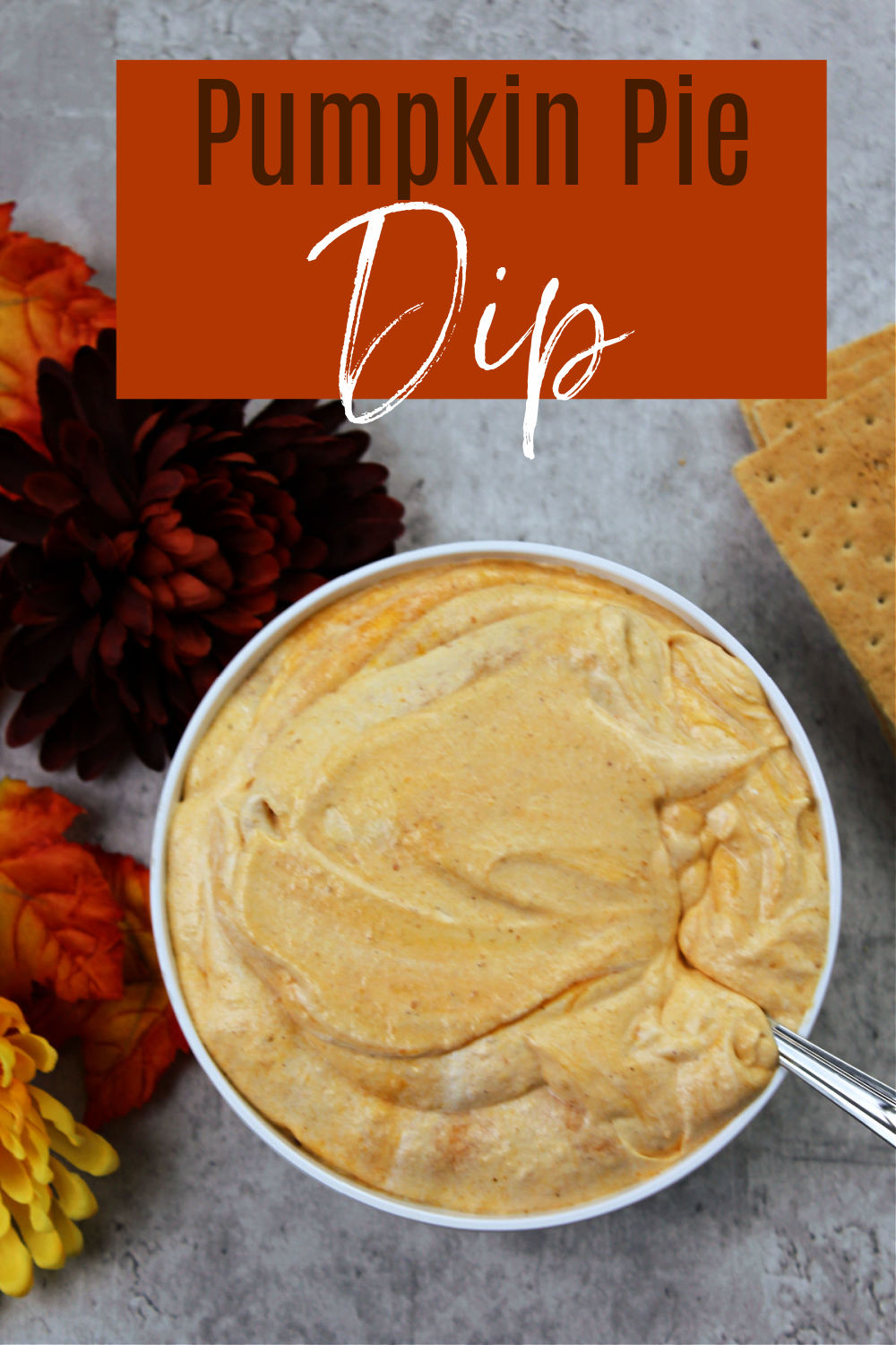 bowl of pumpkin pie dip with a spoon, flowers and crackers nearby.