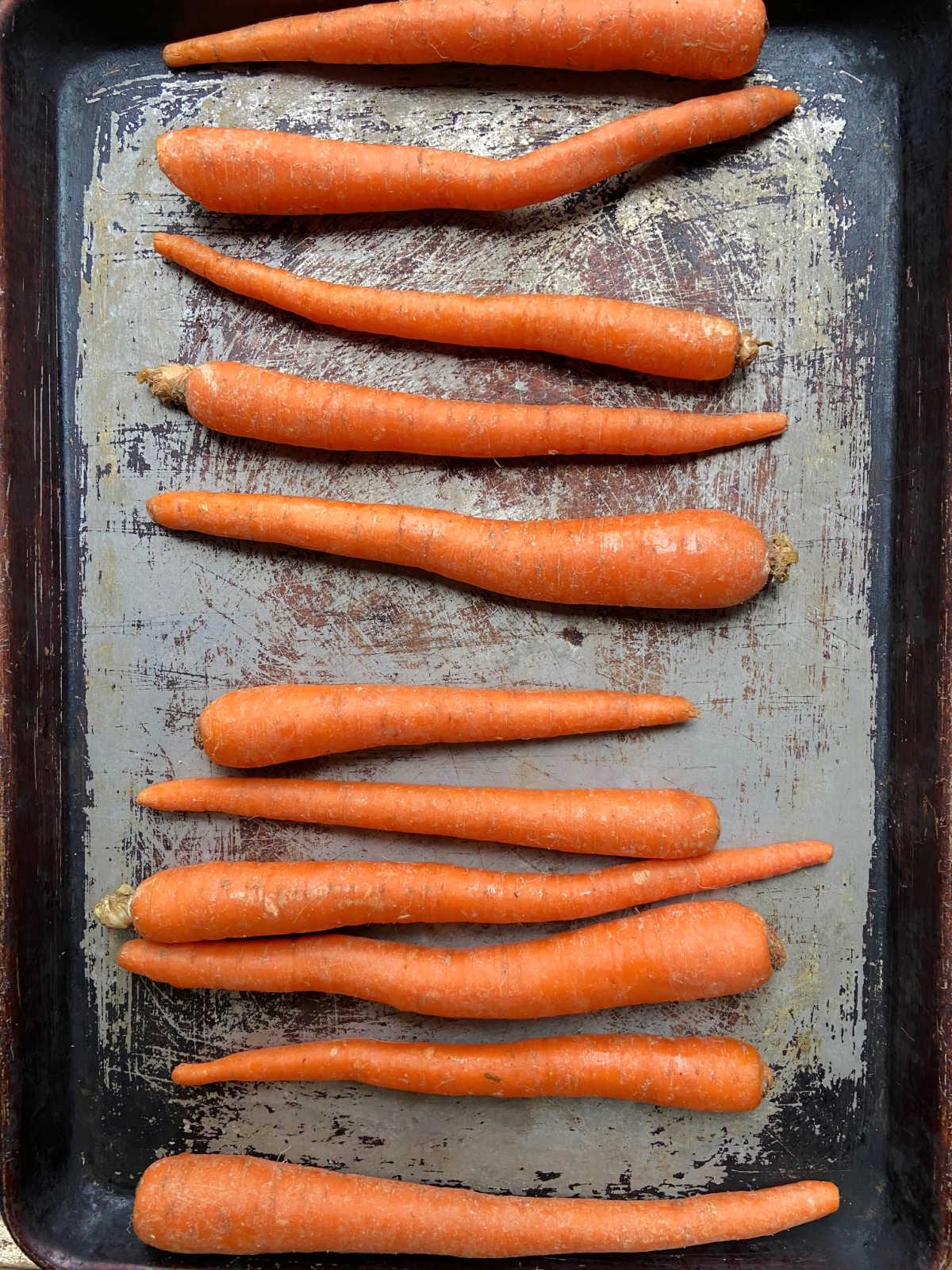 raw carrots on a baking sheet.