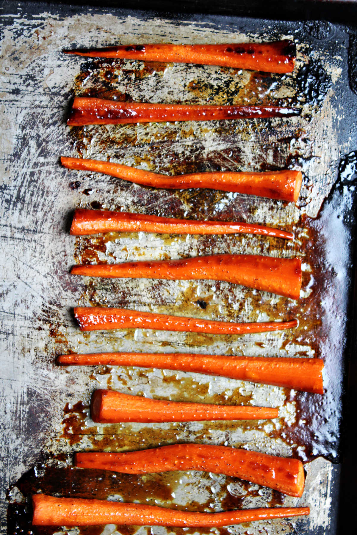 Oven baked carrots ready to eat on a baking sheet.