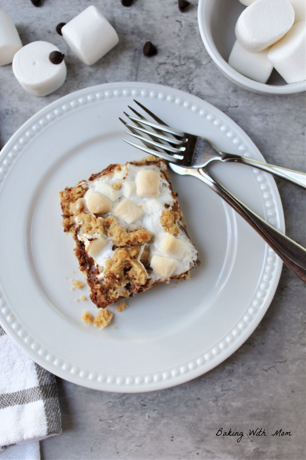 white plate with S'mores bar on top and marshmallows laying besides.